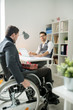 Disabled businessman sitting in wheelchair and moving to his colleague's table he is going to congratulate him with Christmas