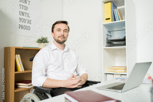 Poster Portrait of confident businessman sitting in wheelchair at his workplace with laptop at office