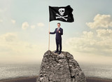 Successful businessman on the top of a mountain holding pirate flag  - 243036911