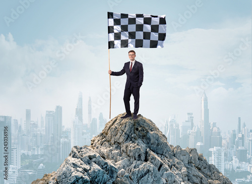 Leinwanddruck Bild Successful businessman on the top of a city holding goal flag