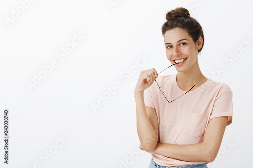 Leinwandbild Motiv Cute and tender young charismatic female with bun hairstyle biting frame of glasses smiling joyfully tilting head as flirting gazing at camera cheerful with positivity over white background