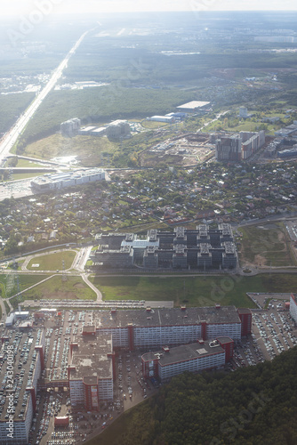 view from the window of the aircraft at dawn over the city, fields, forests, houses, shadows from the clouds, beautiful views of residential areas with houses, forest strips (vertically) - 243040198