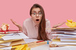 Emotive young European woman with dark hair, feels puzzled and hesitant, opens mouth with bewilderment, wears spectacles and shirt, has stack of papers and books, isolated over pink background