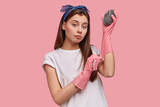 Waist up shot of pleasant looking young woman wears rubber protective gloves, uses two sponges, cleans hotel, dressed in white casual t shirt, isolated over pink background. Housework concept - 243059322