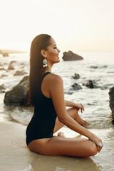Woman On Beach. Girl In Black Swimsuit Sitting On Sea Coast © puhhha