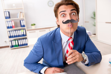 Funny bisinessman with fake moustache in the office