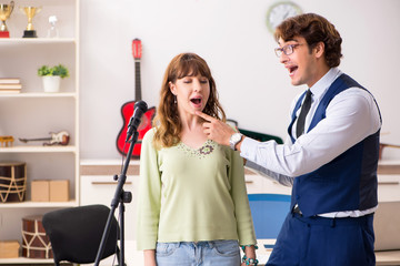 Young woman during music lesson with male teacher © Elnur