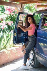 Young woman in a camper van in a beautiful camping with pink flowers © javiindy