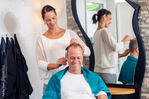 female hairdresser cutting hair of man