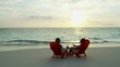 Romantic couple relaxing on chairs Caribbean at sunset
