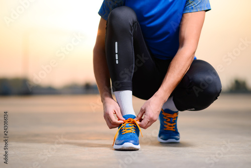 Leinwandbild Motiv Young Male Sportsman Tying Running Shoes and Preparing for Urban Run at Sunset. Healthy Lifestyle and Sport Concept.