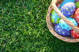 Flat lay shot of Easter eggs in the wicker basket on green spring grass. Space for text - 243091171
