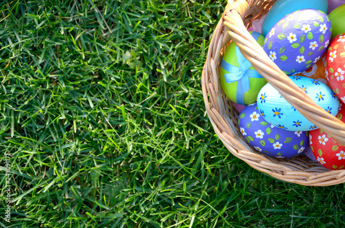 Flat lay shot of Easter eggs in the wicker basket on green spring grass. Space for text © Olena Mykhaylova