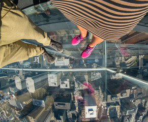 Tourists posing on a glass floor