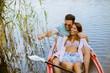Leinwanddruck Bild - Loving couple rowing on the lake