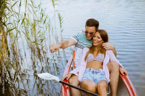 Leinwanddruck Bild Loving couple rowing on the lake