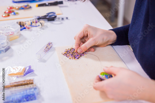 Professional jewelry designer making handmade brooch with beads in studio, workshop. Fashion, creativity and handmade concept © happy_finch