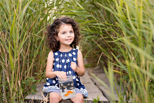 A beautiful girl caught a goldfish and wants to make her wishes. The girl on the pier with a goldfish in a glass jar