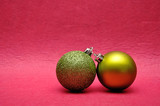 Two green Christmas tree baubles on a pink background - 243107357