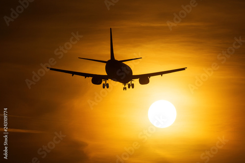 Silhouette of an air plane near to the sun with beautiful red clouds in background - 243109774