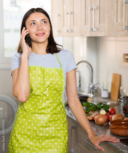 Leinwanddruck Bild Young girl housewife in apron talking by phone at home kitchen