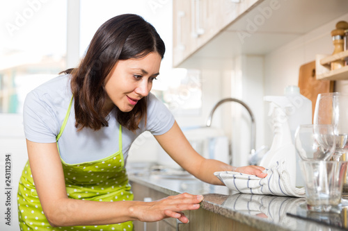 Leinwanddruck Bild Woman housewife in apron cleaning furniture at home kitchen