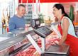 Leinwanddruck Bild - Adult seller helping male choosing sausages