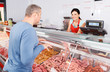 Leinwanddruck Bild - seller helping attentive customer choosing different sausages