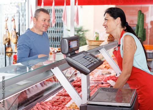 Leinwanddruck Bild Adult seller helping male choosing sausages
