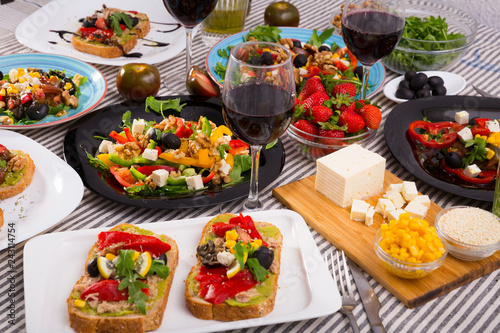 Many plates with different vegetarian food and  glass of wine - 243114754