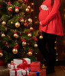pregnant woman posing in christmas lights, red dress, holiday concept