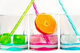 On a white background glasses in rainbow colors with colored ice, and cold water and fresh pieces of orange - 243121187