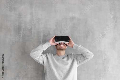 Leinwandbild Motiv Handsome man playing video games in VR goggles or 3d glasses, wearing virtual reality headset for on his head