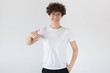 Leinwandbild Motiv Smiling nice woman pointing at her blank white t-shirt with index finger, copy space for your advertising, isolated on gray background