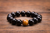 Bracelet from round black stones lying on a wooden background.
