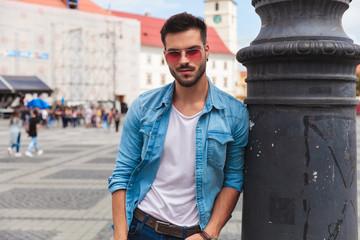 relaxed man in denim shirt leans against lighting pole