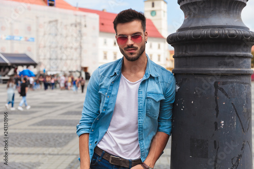 Leinwandbild Motiv relaxed man in denim shirt leans against lighting pole