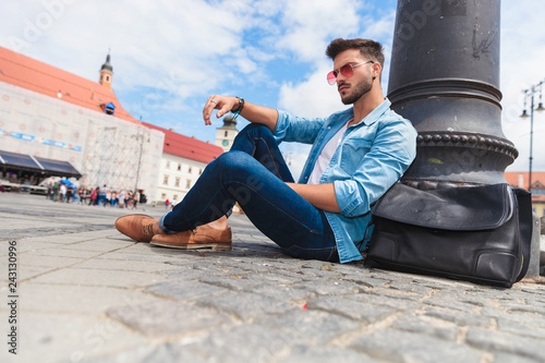 Leinwanddruck Bild casual man sitting near lighting pole on urban background