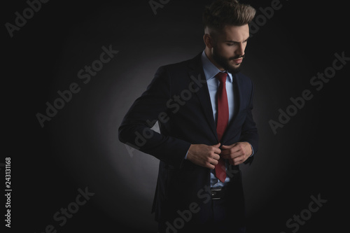 Leinwandbild Motiv attractive businessman buttons navy suit and looks down to side