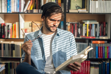 Male student sitting on a chair and with book in one hand and eyeglasses in other.
