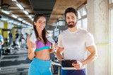 Picture of personal fitness trainer and his female client in gym posing in front of the camera. - 243141518