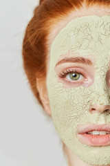 awesome ginger girl with cosmetic green mask on face. close up photo. beauty concept