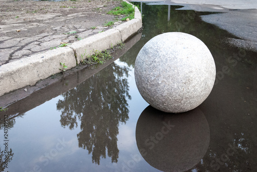 Large ball of granite in a puddle, in the park, on the background of asphalt and curb stone, in the reflection of the water trees and sky