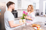 Waist up portrait of happy young couple at home in kitchen, focus on smiling woman holding bouquet of pink roses - 243150729