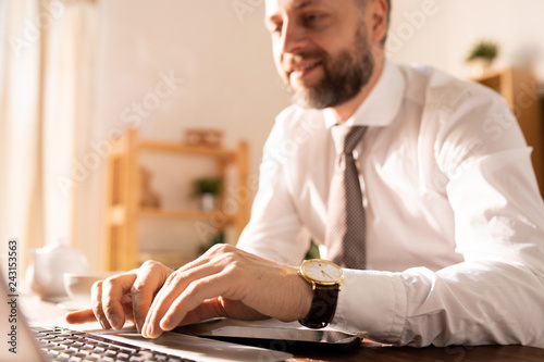 Close-up of content successful businessman with wristwatch sitting at table and typing on laptop while working with online report at home