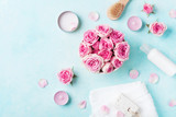 Aromatherapy, spa, beauty background with roses flowers, cosmetics and candles on blue table. Flat lay style. - 243158337