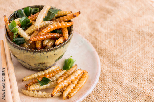 Leinwandbild Motiv Food Insects: Bamboo worm (Bamboo Caterpillar) insect fried crispy for eating as food items on plate with chopsticks on sackcloth, it is good source of protein edible for future food concept.