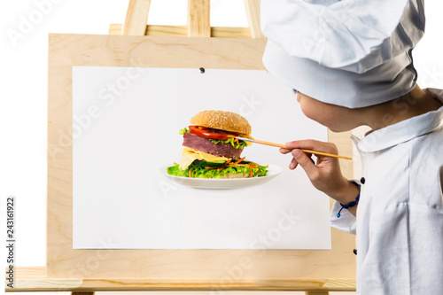 Poster cute boy in chef uniform preparing with a brush on paper an appetizing sandwich on a white background