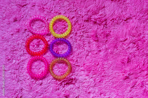 bunch of plastic cable hair elastics in different colors isolated on a soft pink background, girl hair accessories - 243163924