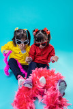 Little twin sisters having holiday mood while playing with pink boa - 243164342